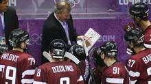 Latvia's head coach Ted Nolan, left, listens as an assistant coach draws up a play during the third period of a men's quarter-final game against Canada (Mark Humphrey/The Associated Press)