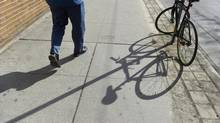 A pedestrian walks by a bike locked to a sign post on King St. West in this file photo. Lisa Ferguson said her bicycle was locked to a pole at the northeast corner of Yonge and Bloor streets, but was gone when she returned. (Fred Lum/The Globe and Mail)