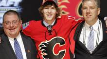 Mark Jankowski, center, a center, stands with Calgary Flames officials after being chosen 21st overall in the first round of the NHL draft on Friday, June 22, 2012, in Pittsburgh. (Keith Srakocic/AP)