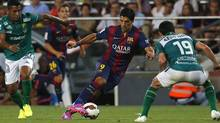 Barcelona's Luis Suarez from Uruguay fights for the ball against Leon's Luis Antonio Delgado, left, and Jonny Magallon, during the Joan Gamper trophy friendly soccer match between Barcelona and Leon at the Camp Nou stadium in Barcelona, Spain, Monday, Aug. 18, 2014. (Emilio Morenatti/AP)
