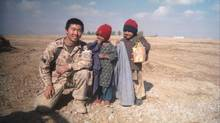Corporal David Hawkins poses with children in Afghanistan in a 2008 photo. Cpl. Hawkins was let go in October, 2013, on a medical discharge after begging for months to remain until he'd hit the 10-year mark of service. (CPL. DAVID HAWKINS/THE CANADIAN PRESS)