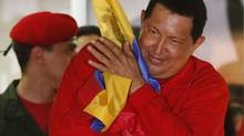 Venezuelan President Hugo Chavez hugs the national flag while celebrating from a balcony at the Miraflores Palace in Caracas October 7, 2012. (JORGE SILVA/REUTERS)