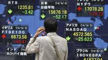 A man looks at an electronic board displaying Japan's Nikkei average (top, centreC) and the stock price indexes of various countries outside a brokerage in Tokyo Sept. 4, 2014. (ISSEI KATO/REUTERS)