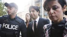 Police escort former CBC radio host Jian Ghomeshi, centre, who appears with his lawyer Marie Henein, right, for his pre-trial hearing for his sexual assault case in Toronto. (Michelle Siu/The Canadian Press)