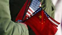 An onlooker holds the U.S. and Chinese flags as President Barack Obama welcomes Chinese President Hu Jintao during at the White House in Washington on Jan. 19, 2011. (JEWEL SAMAD/AFP/Getty Images)