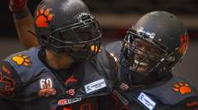 B.C Lions running back Andrew Harris (L) celebrates his touchdown against the Calgary Stampeders with teammate Rolly Lumbala during the first half of their CFL football game in Vancouver, British Columbia, August 17, 2013. The Lions made a surprise uniform switch prior to the start of the game. (BEN NELMS/REUTERS)