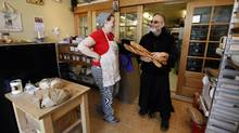 Stephanie Smith laughs with Father Roberto Ubertino, executive director of St. John the Compassionate Mission and St. John's Bakery (Deborah Baic/The Globe and Mail/Deborah Baic/The Globe and Mail)