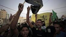 Palestinians chant slogans as they gather to celebrate the ceasefire in Gaza City Aug. 26, 2014. (Khalil Hamra/Associated Press)