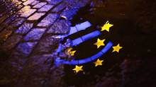 The Euro sculpture is reflected in a puddle on cobblestone pavement in front of European Central Bank headquarters in Frankfurt on Jan. 21, 2012. (KAI PFAFFENBACH/REUTERS)