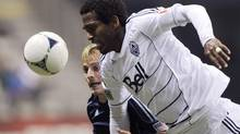 Sporting KC Seth Sinovic (blue) heads the ball against Vancouver Whitecaps Atiba Harris during the second half of their MLS soccer match in Vancouver, British Columbia April 18, 2012. (BEN NELMS/REUTERS)