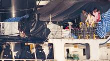 Some the estimated 490 people thought to be Tamil migrants aboard the ship MV Sun Sea peer out from underneath a tarp after Canadian Border officials and police brought the ship into Canadian Forces Base Esquimalt in Colwood, British Columbia on Vancouver Island August 13, 2010. (ANDY CLARK/REUTERS/ANDY CLARK/REUTERS)