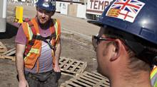 Temporary foreign worker David Beattie,left, from Scotland and Thomas Sutton from England take a break from working on the construction of a new police station in Edmonton. (JASON FRANSON FOR THE GLOBE AND MAIL)