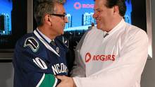 Rogers Communications CEO Nadir Mohamed, left, wearing a Vancouver Canucks jersey, shakes hands with Vancouver Canucks and Rogers Arena owner Francesco Aquilini, wearing a Rogers jersey, after announcing that General Motors Place is now named Rogers Arena in Vancouver, B.C., on Tuesday July 6, 2010. The arena had been called GM Place since it opened in 1995. (THE CANADIAN PRESS/Darryl Dyck)