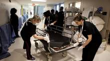 Cleaners wipe down a bed at the new Bridgepoint Hospital in Toronto on April 14, 2013. (Matthew Sherwood For The Globe and Mail)