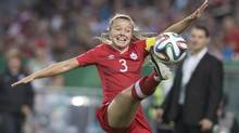 Canada's captain Kinley McNicoll brings the ball under control as coach Andrew Olivieri looks on during first half action in 2014 FIFA U-20 Women's World Cup action against Finland in Toronto on Friday August 8. (Chris Young/THE CANADIAN PRESS)