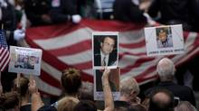 People hold up photos of victims during a memorial service at the 9/11 memorial September 1, 2016 in New York. The United States on Sunday commemorated the 15th anniversary of the 9/11 attacks. (BRENDAN SMIALOWSKI/AFP/Getty Images)