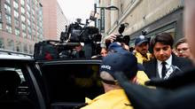 Former CBC radio personality Jian Ghomeshi makes his way past a crush of media while leaving court in Toronto on Jan. 8, 2015.