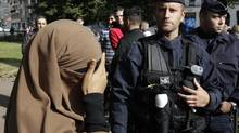 A woman wearing a full-face veil, or niqab, covers her eyes as she stands near police during an identity check when she arrived to demonstrate after calls on the internet by Islamic groups to protest over an anti-Islam video, in Lille September 22, 2012. In France, the publication of cartoons denigrating the Prophet Mohammad have stoked anger over an anti-Islam video and the authorities have banned all protests over the issue. It is illegal to wear face-covering headgear in France. (© Pascal Rossignol //REUTERS)