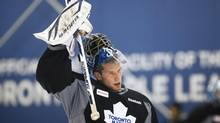 Toronto Maple Leafs goaltender James Reimer puts on his face mask during the team's training camp in Toronto on Sunday, January 13, 2013. (Michelle Siu/THE CANADIAN PRESS)