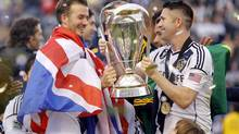 Los Angeles Galaxy's Robbie Keane (R) hands teammate David Beckham (L) the trophy after the Galaxy defeated the Houston Dynamo to win the MLS Cup (DANNY MOLOSHOK/REUTERS)
