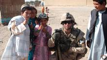 Cpl. Jamie McMullin with children in Afghanistan. He died by suicide after returning from war. (Courtesy McMullin family)