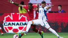Canada's Doneil Henry, left, and El Salvador's Nelson Bonilla vie for the ball during first half FIFA World Cup qualifying soccer action in Vancouver, B.C., on Tuesday September 6, 2016. (DARRYL DYCK/THE CANADIAN PRESS)