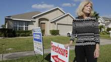 A real estate agent stands in front of a foreclosed home in Kissimmee, Fla. (Phelan M. Ebenhack/AP)