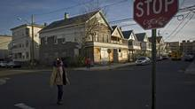 A man crosses the street in front of abandoned houses near Main Street in Bridgeport, Conn. (NEVILLE ELDER FOR THE GLOBE AND MAIL)