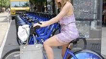 Jocelyn Steiber, the owner of Jost Social Media, wears wedges while riding a Citi Bike in New York, June 27, 2013. (CASEY KELBAUGH/NYT)