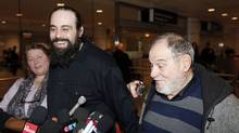 Canadian Greenpeace activist Alexandre Paul, centre, smiles as he meets the media with his parents after arriving at Montreal's airport on Dec. 27, 2013. Mr. Paul spent about two months in prison after being arrested during a protest outside a Russian oil rig in the Arctic. (Christinne Muschi/Reuters)
