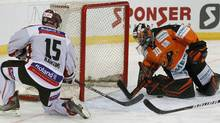 Dinamo Riga's Martins Karsums shoots to score as goalkeeper Daniar Dshunussow (R) of Grizzly Adams Wolfsburg tries to defend during their semi-final game at the Spengler Cup ice hockey tournament in the Swiss mountain resort of Davos December 30, 2011. REUTERS/Arnd Wiegmann (Arnd Wiegmann/Reuters)