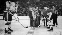 Prime minister Pierre Trudeau drops the puck for Canada's Phil Esposito, right, and Soviet winger Vladimir Vikulov to open the 1972 hockey series. (Peter Bregg)