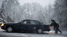 Two men push a car on a slick road as snow falls in Putney, Vermont October 29, 2011. Freezing conditions prevailed on the US East Coast Sunday after a rare October snowstorm and icy rain reportedly killed at least three people, sparked long airport delays and caused massive power outages. (Don Emmert/AFP/Getty Images/Don Emmert/AFP/Getty Images)