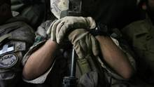 A Canadian soldier in Afghanistan rests on the muzzle of his rifle as he sleeps while riding in an armoured vehicle in Kandahar province in 2007. A Globe and Mail investigation revealed that 54 Afghan war veterans had taken their own lives, a toll that has now grown to 71. (FINBARR O'REILLY/REUTERS)