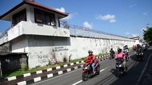 Motorcyclists ride their vehicles past the Kerobokan prison in Denpasar on Indonesia's resort island of Bali on June 19, 2017. (SONNY TUMBELAKA/AFP/Getty Images)