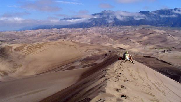 A hiker summits a dune and views the panorama of the Great Sand Dunes National Preserve in Colorado.