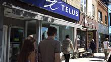 Pedestrians walk by a Telus store in Toronto on Aug. 15, 2013. Experts say an upcoming wireless auction won't result in increased competition. (Galit Rodan/The Canadian Press)