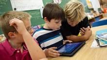 Nicklaus O' Rourke, left, Noah Dobbiestamos and Owen Hakker play with an iPad. (GEOFF ROBINS/Geoff Robins for The Globe and Mail)