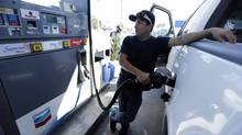 Chris King fills up his truck at a gas station in San Diego. (Gregory Bull/The Associated Press)