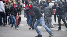 A demonstrator throws a rock towards the police line during a student demonstration outside the Montreal Convention Centre against hikes to university and college tuition fees Friday, April 20, 2012 in Montreal. (Paul Chiasson/THE CANADIAN PRESS)