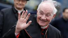 Cardinal Marc Ouellet waves Wednesday as he arrives for a meeting at the Synod Hall in the Vatican. (Reuters)