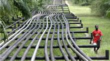In this file photo, an unidentified man walks along oil pipelines belonging to Italian oil company Agip in Obrikom, Nigeria on Monday, March 6, 2006. (GEORGE OSODI/ASSOCIATED PRESS/GEORGE OSODI/ASSOCIATED PRESS)