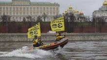 Greenpeace International activists on an inflatable boat pass by the Kremlin along the Moskva River on Nov. 6, 2013, protesting against Russia's detention of members of the environmental group. (Alexander Zemlianichenko/Associated Press)