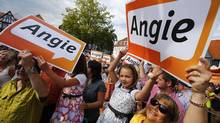 Supporters of German Chancellor Angela Merkel hold up placards during a election campaign rally in Seligenstadt near Frankfurt. (Ralph Orlowski/Reuters)