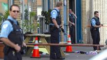 Police officers investigate a crime scene after a shootout in east-end Montreal left two men dead on Tuesday, June 29, 2010. (Alain Roberge/The Canadian Press/Montreal La Presse/Alain Roberge/The Canadian Press/Montreal La Presse)