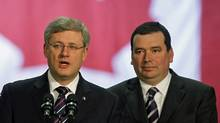 Prime Minister Stephen Harper and Minister of Natural Resources Christian Paradis speak to workers in Thetford Mines, Que., on Dec. 13, 2010. (SHAUN BEST/Reuters)