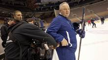 An HBO 24/7 sound crew member turns Toronto Maple Leafs Head Coach Randy Carlyle's microphone on during Leafs practice at the Air Canada Centre. (Deborah Baic/The Globe and Mail)