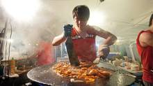 Eddie Jiang makes barbecued squid for the Barcode Chinese Restaurant food stall during the Night It Up! Asian night market in Markham, Ont., on July 16, 2011. (JENNIFER ROBERTS FOR THE GLOBE AND MAIL/JENNIFER ROBERTS FOR THE GLOBE AND MAIL)