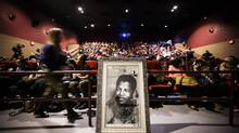 A portrait of Nelson Mandela is seen as people take their seats before a screening of Long Walk to Freedom, a film about the South African leader's life,­ put on by the Nelson Mandela Public School at a theatre in Toronto on Dec. 5, 2013. (MARK BLINCH FOR THE GLOBE AND MAIL)