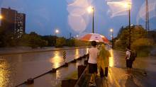 A group of people take pictures of the flooding from torrential rain which caused the closure of the Don Valley Parkway in Toronto on July 08, 2013. (Deborah Baic/The Globe and Mail)